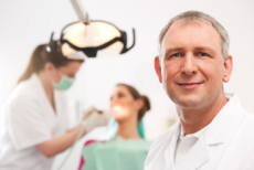 Man smiling while at his back an dentist check up